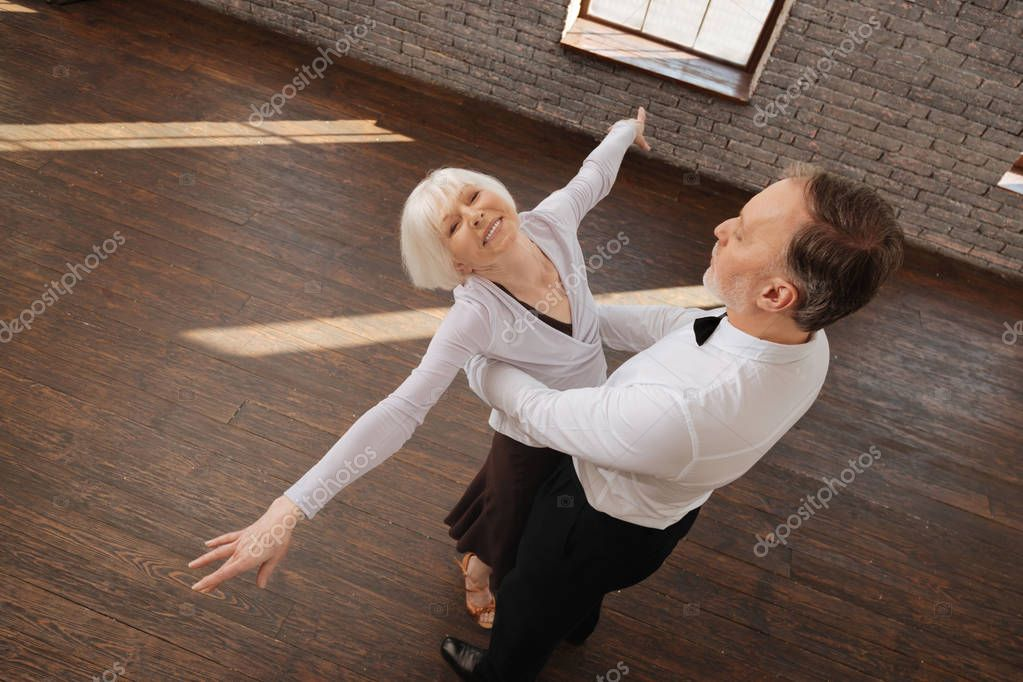 Optimistic retired dance couple enjoying waltz in the dance studio