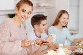 Cheerful caring mother having breakfast with her children