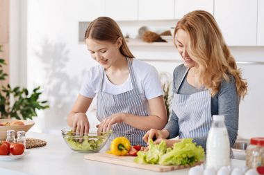 Positive girl and her mother enjoying cooking together