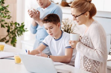 Caring mother checking home assignment of her son