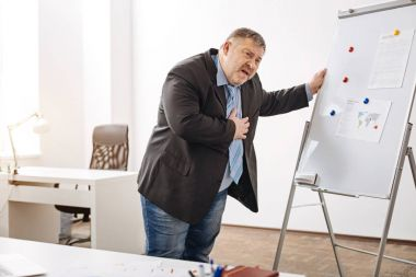 Hard working businessman having a heart stroke