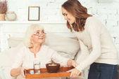 Fotografie Pozitivní mladá vnučka péče o důchodce doma