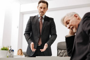 Puzzled coworker having difficulties in conversation with colleague