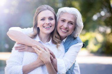 elderly mother hugging woman in park