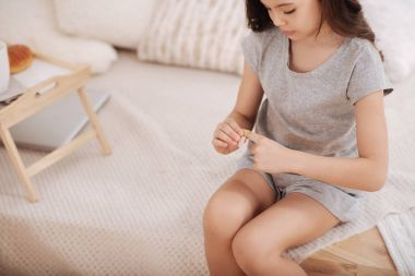 Confident child putting medical patch on the finger at home