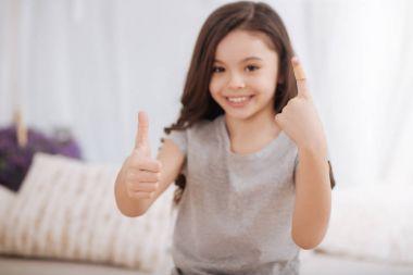 Sunny little girl demonstrating injured finger at home