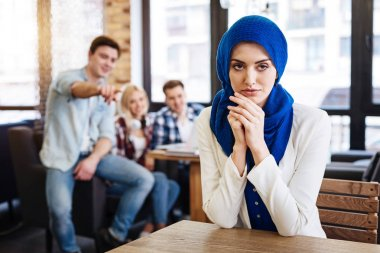 Beautiful pleasant muslim woman sitting in the cafe