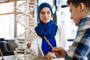 Positive muslim girl studying genetics with her groupmate