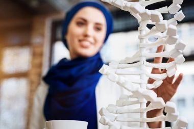 Selective focus of DNA model in hands of muslim student
