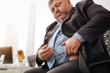 Corpulent office worker giving himself daily injection
