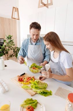 Top view of cheerful father and daughter cooking salad