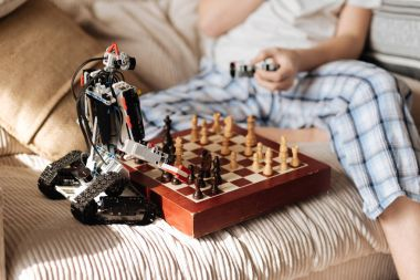 Close up of toy robot standing near chess board