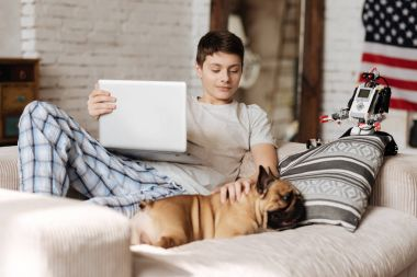 Delighted youngster putting left hand on his dog