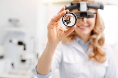 professional female doctor using indirect ophthalmoscope