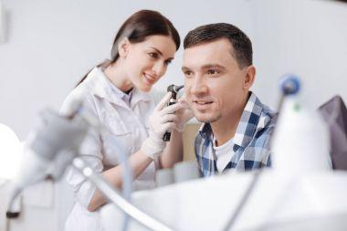 otolaryngologist touching ear of her patient