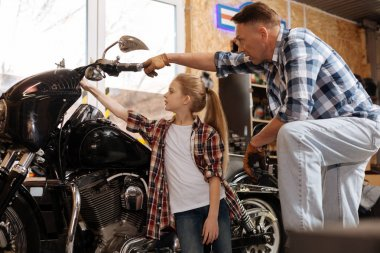 Cute passionate kid being fascinated by huge motorbike