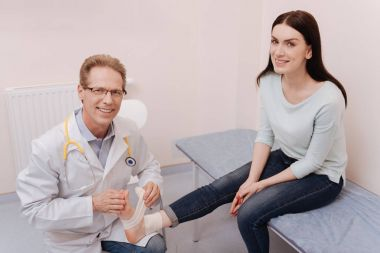 Friendly professional rheumatologist happy assisting his patient