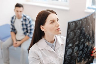 Serious female neurologist examining the X ray photo
