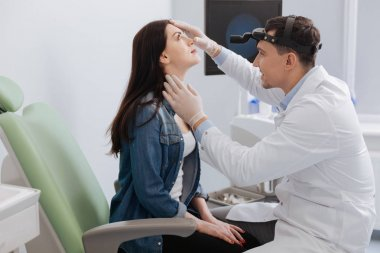 Positive otorhinolaryngologist checking nose of his patient