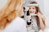 Fotografia Abile oculista addestrato esaminando vista ragazze