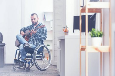 Distracting from all problems. Gifted capable young disabled sitting on the wheelchair indoors and enjoying free time while playing the guitar stock vector