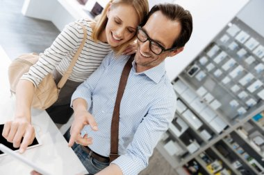 Adorable couple smiling while taking selfies at shop