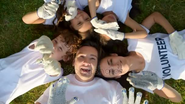 Více dobrovolníků, kterým se na trávě a mává do kamery ve věku