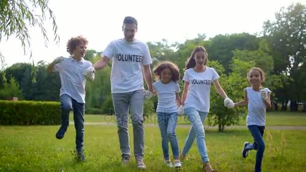 Skupina dobrovolníků zářící skákání a zábava venku