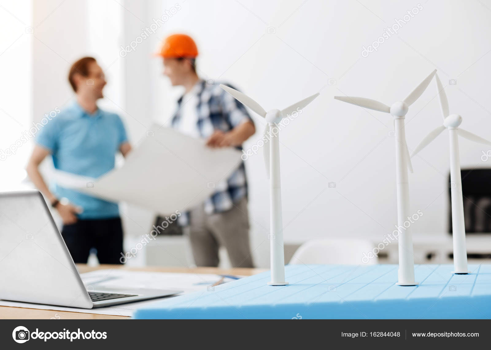 Engineer discussing a power station blueprint with a builder stock young builder in a hard hat standing the background holding a big blueprint and discussing it with an engineer while the focus being on three wind turbine malvernweather Images