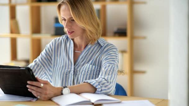 Veselá mladá žena dělat poznámky při studiu doma