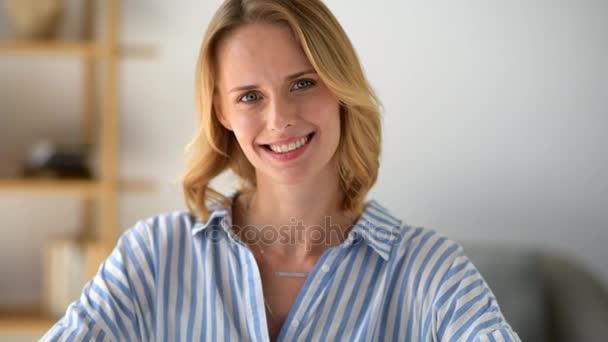 Okouzlující mladá dáma pózuje pro kameru a usmívá se