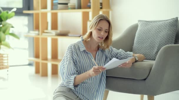 Beautiful young lady checking business documents at home