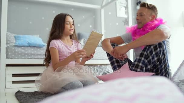 Roztomilá holčička čtení pohádek se svým otcem