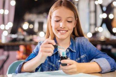 Cheerful teenage girl holding open nail polish bottle