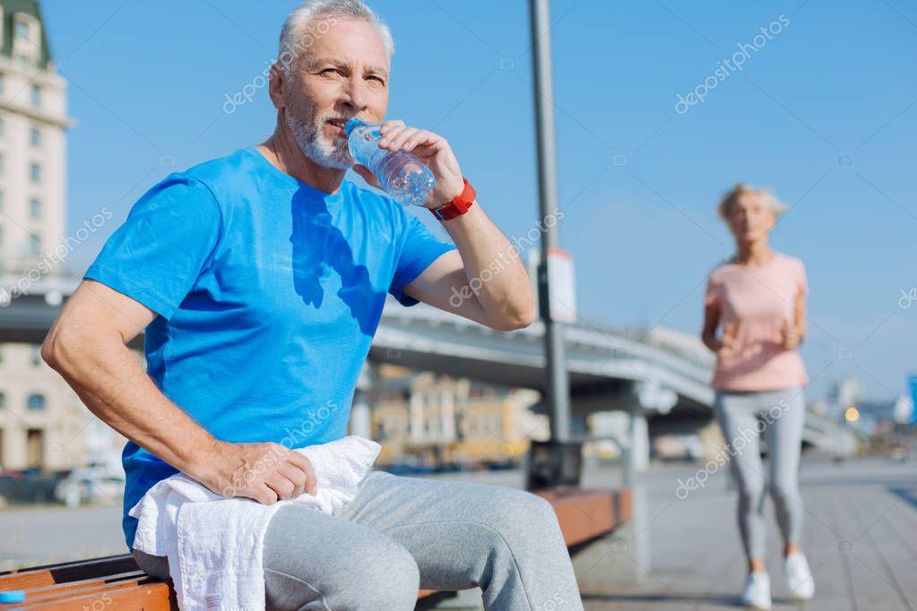 Senior man drinking water after workout