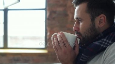 Scaled up of relaxed millennial guy in scarf drinking tea