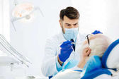 Attentive dental surgeon curing the patient