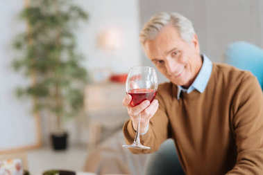 Happy old man enjoying his glass of red wine