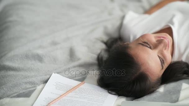Veselá mladá žena odpočívá v její ložnici