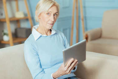 Curious aged woman sitting on a sofa and holding a modern tablet