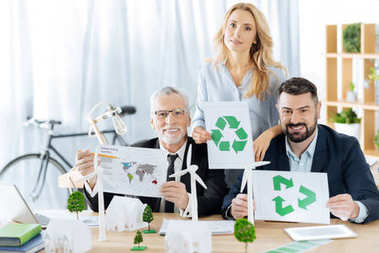 Saving planet. Clever friendly eco friendly engineers sitting together and showing recycling symbols while working at the important ecological project stock vector