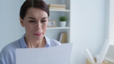 Poor young woman crying after looking at dismissal notice