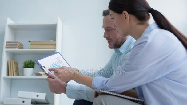 Two office employees talking over statistics in office