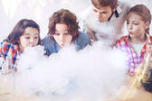 Photo Group of children blowing on fume during chemistry experiment