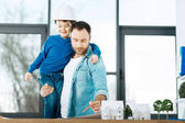 Fotografie Angenehme Architekt hält seinen Sohn während der Arbeit