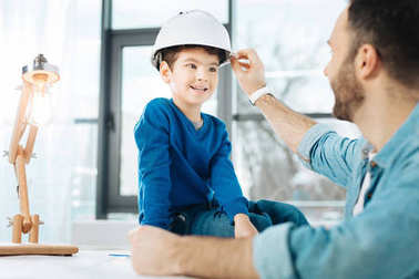 Caring father fixing hard hat on his sons head