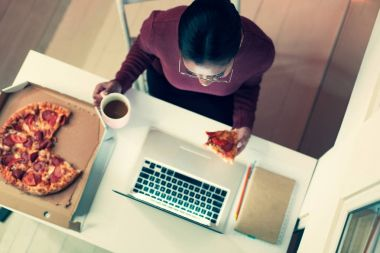 Top view of young woman eating pizza while working