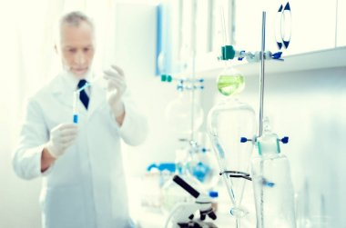 Male lab worker conducting chemical experiment