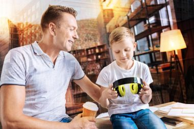 Cheerful man drinking coffee while his son holding big headphones