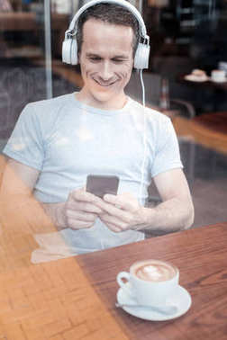 Handsome young man looking at his smartphone